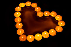 Burning candles. Burning candles in the shape of heart close up in the dark Royalty Free Stock Images