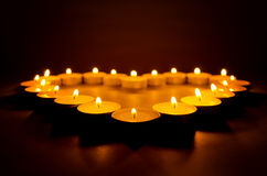 Burning candles. Burning candles in the shape of heart close up in the dark Royalty Free Stock Photos