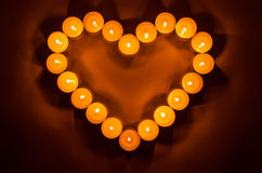 Burning candles. Burning candles in the shape of heart close up in the dark Royalty Free Stock Photo
