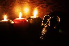 Burning candles and skull on black background stock image