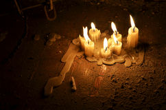 Burning candles. Some old candle burning down on the table in a dark room Royalty Free Stock Photo