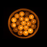 Burning candles in straw dish isolated on black Royalty Free Stock Photos