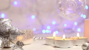 Burning candles and a suspended Christmas ball with luminous blue lanterns in the background, large-scale plan stock footage