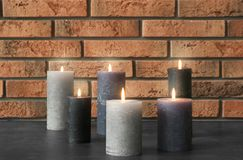 Burning candles on table. Against brick wall stock photography
