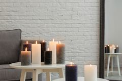 Burning candles on tables. In living room stock image