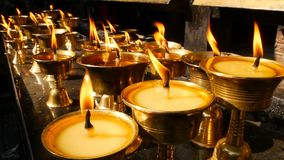 Burning candles in temple. View of golden shiny bowls with burning flame of oil candles for worship. Burning candles in temple. View of golden shiny bowls with stock video footage