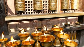 Burning candles in temple. View of golden shiny bowls with burning flame of oil candles for worship. Burning candles in temple. View of golden shiny bowls with stock video