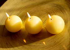 Burning candles. Three round, burning candles, and the shiny surface of the table Royalty Free Stock Images