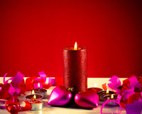 Burning candles with two heart shaped toys Royalty Free Stock Image
