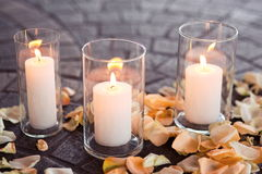 Burning candles in a vase with rose-leafs stock photos