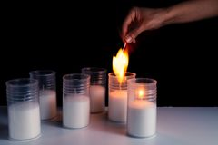 Burning candles on a white background next to the fireworks. Obon festival. Diwali festival. Hand lights candles. Burning candles on a white background next to royalty free stock image