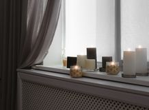 Burning candles on window sill. In room royalty free stock photography