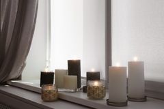 Burning candles on window sill. In room stock photo