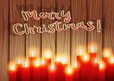 Burning candles on a wooden background. Merry Christmas and Happy New Year greeting card. Xmas letter Stock Photo