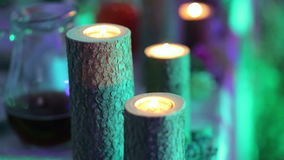 Burning candles on wooden stumps in the wedding decor. stock video footage