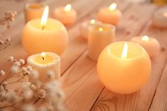 Burning candles on table. Burning candles on wooden table royalty free stock image