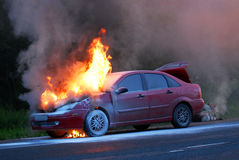 Burning car. The car is burning on the roadway Royalty Free Stock Photography