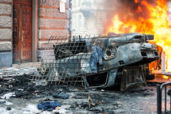 Burning car. car destroyed and set on fire during the riots. city center. Car destroyed and set on fire during the riots. city center. clouds of smoke Royalty Free Stock Image