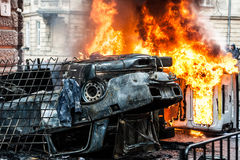 Burning car. car destroyed and set on fire during the riots. city center. Car destroyed and set on fire during the riots. city center. clouds of smoke Stock Photography