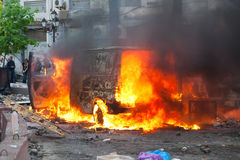 Burning car in the center of city during unrest Stock Image