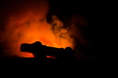 Burning car on a dark background. Car catching fire, after act of vandalism or road indicent. Burning vintage car nightshot Stock Photo