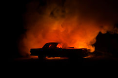 Burning car on a dark background. Car catching fire, after act of vandalism or road indicent. Burning vintage car nightshot Royalty Free Stock Photo
