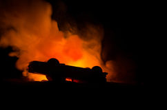 Burning car on a dark background. Car catching fire, after act of vandalism or road indicent. Burning vintage car nightshot Stock Image