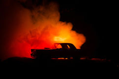 Burning car on a dark background. Car catching fire, after act of vandalism or road indicent. Burning vintage car nightshot Royalty Free Stock Image