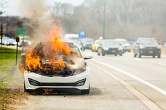 Burning car on fire on a highway road accident. At day royalty free stock images