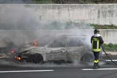 Burning car with firefighters Stock Photography