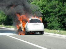 Burning car on highway. Rear view of burning motor car on highway Royalty Free Stock Photography