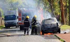 Burning car on the road with fire department stock photo