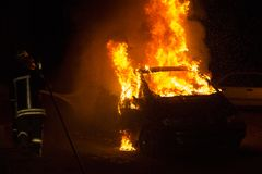 Burning car on the road in the night. Fire fighters at work Royalty Free Stock Image