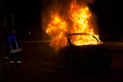 Burning car on the road in the night. Fire fighters at work Royalty Free Stock Images