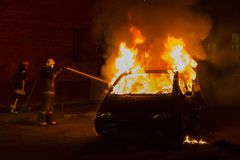 Burning car on the road in the night. Fire fighters at work Royalty Free Stock Photography