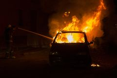Burning car on the road in the night. Fire fighters at work Stock Photo