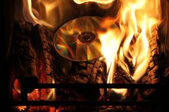 Burning CD/DVD. CD/DVD burning on a wood log fire with flames all around royalty free stock photography