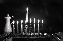 Burning Chanukah. The lit Chanukiah. Jewish holiday Hanukkah. Black and white photo. Porcelain jug with oil. Burning Chanukah. The lit Chanukiah. Jewish holiday stock image