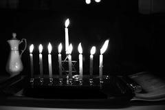 Burning Chanukah. The lit Chanukiah. Jewish holiday Hanukkah. Black and white photo. Porcelain jug with oil. Burning Chanukah. The lit Chanukiah. Jewish holiday stock photography