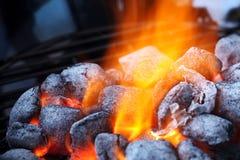 Burning charcoal briquettes closeup. Closeup of charcoal briquettes and flames Royalty Free Stock Photos