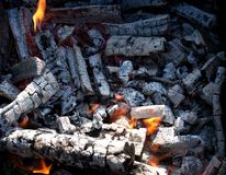Burning charcoal embers firewood with ashes and Royalty Free Stock Photo