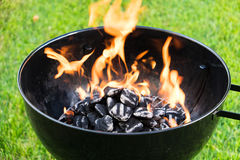 Burning Charcoal in a Grill. Close up on a lawn background Stock Photos