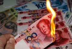 Burning Chinese yuan. On a pile of different currencies stock photography