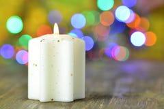 Burning Christmas candle on magical bokeh background Stock Image