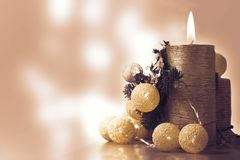 Burning Christmas Candle and some lighting decoration against a white blured background with some bokeh effect. royalty free stock photos
