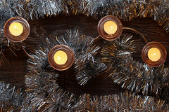 Burning Christmas candles. In candlesticks between the garland Royalty Free Stock Photo