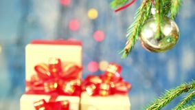 Burning Christmas candles and gifts with red bows are blurred and the focus turns to a decorated branch. stock video footage