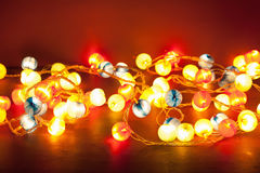 Burning christmas lights over red background Stock Photography