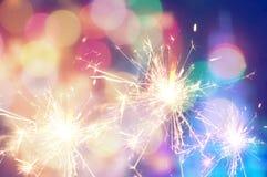 Burning christmas sparkler on colorful light background Royalty Free Stock Photos