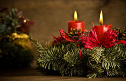 Burning christmas wreath. Green christmas wreath decorated with red burning candles, red ribbons and golden pine cones on timber floor royalty free stock images